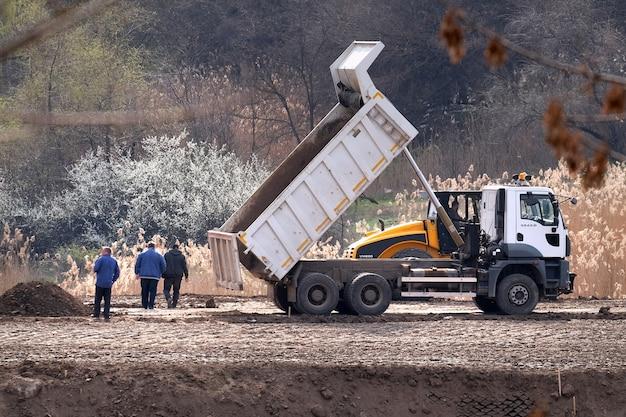 Persone e macchine industriali pesanti costruiscono una nuova strada