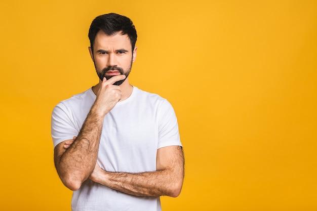 Persone, crisi, emozioni e concetto di stress - uomo barbuto infelice che soffre di mal di testa a casa. isolato su sfondo giallo.