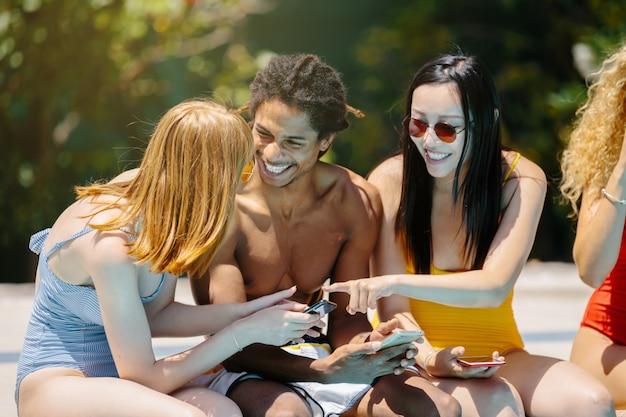 Persone di diverse etnie in costume da bagno seduti sul bordo di una piscina sorridendo e utilizzando i telefoni cellulari