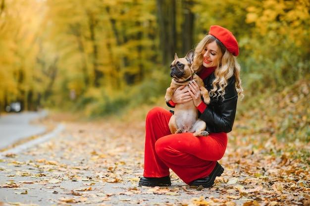 Persone e cani all'aperto. bella e donna felice che si diverte nel parco autunnale che cammina con il suo adorabile bulldog francese.