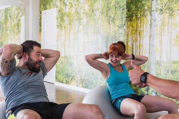 Persone che fanno esercizi di pilates di equilibrio in una palestra con un allenatore che le motiva