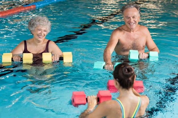 Persone che fanno esercizio con manubri aqua in una piscina