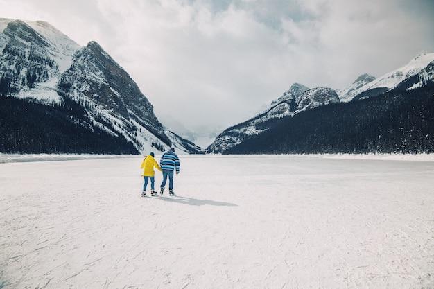 Persone che fanno pattinaggio sul ghiaccio sul lago ghiacciato louise a banff