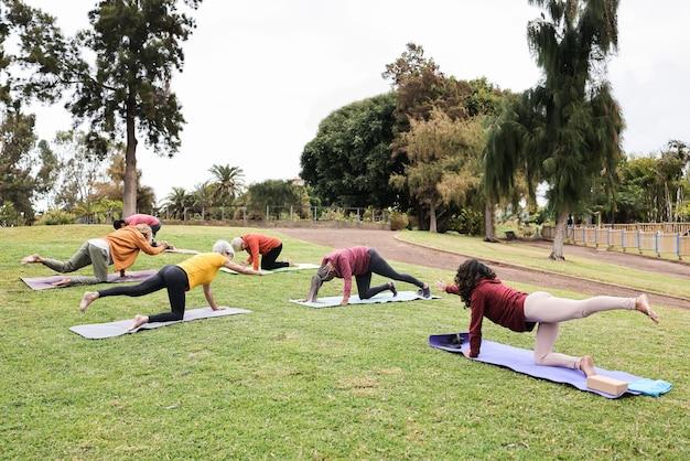 Persone che fanno lezione di yoga mantenendo le distanze sociali nel parco cittadino
