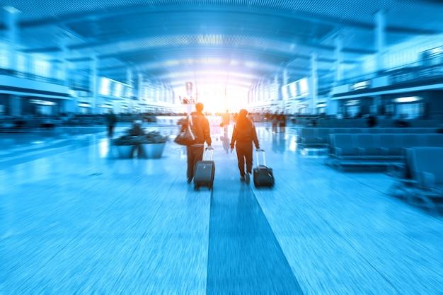 Persone che trascinano i bagagli nella hall dopo la stazione ferroviaria pronte a partire