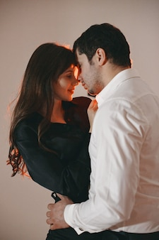 Persone vestite con abiti classici. coppia alla moda in un momento sensuale sul muro bianco.