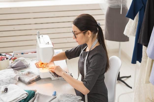 Persone, sarta e concetto di moda - ritratto di vista laterale dello stilista in bicchieri utilizzando la macchina da cucire in officina