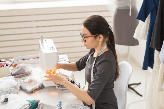 Persone sarta e concetto di moda vista laterale ritratto di stilista in bicchieri utilizzando il cucito