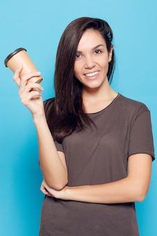 Persone, bevande e concetto di stile di vita - giovane bella donna con caffè su sfondo blu. donna attraente felice e sorridente. una donna con i capelli scuri tiene in mano un bicchiere di cartone con del caffè