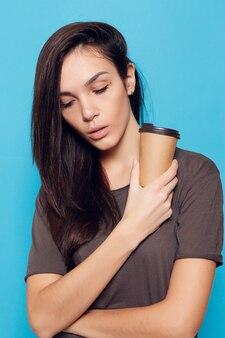 Persone, bevande e concetto di stile di vita - giovane bella donna con caffè sulla superficie blu