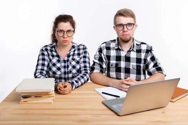 Persone e concetto di educazione due studenti tristi vestiti con una camicia a quadri seduti a un tavolo