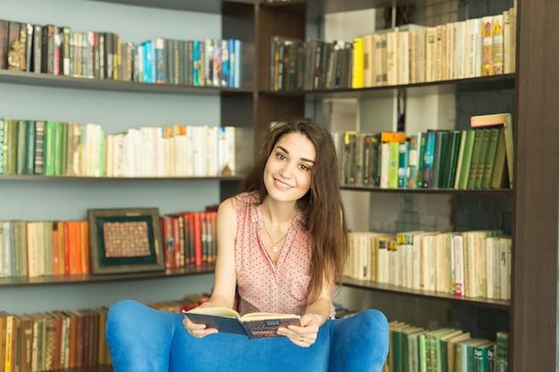 Concetto di persone, istruzione e università - giovane studentessa con un libro in biblioteca