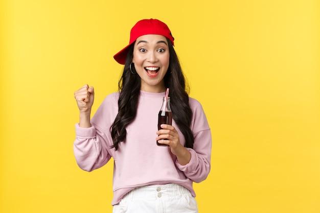 Emozioni della gente, bevande e concetto di svago estivo. ragazza asiatica carina eccitata sorpresa in berretto rosso, bevendo bevande gassate e cantando, guardando la partita sportiva, godendosi le vacanze, sfondo giallo.