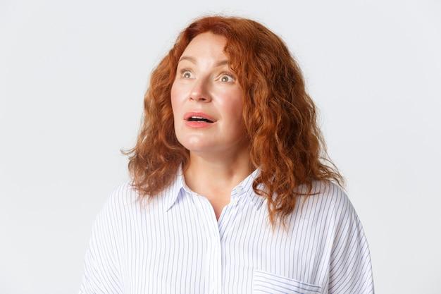 Persone, emozioni e concetto di stile di vita. primo piano di una donna di mezza età dai capelli rossi affascinata e senza parole che reagisce a qualcosa di straordinario nell'angolo in alto a sinistra, muro bianco.