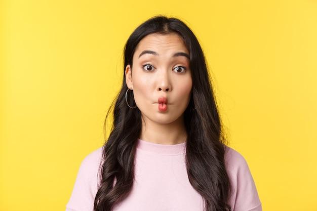 Emozioni delle persone, tempo libero lifestyle e concetto di bellezza. ragazza asiatica sciocca e divertente che fa le labbra di pesce e guarda una macchina fotografica indecisa, mangia qualcosa di acido, in piedi su uno sfondo giallo.