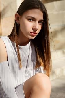 Persone, emozioni, naturale, bellezza e concetto di stile di vita - bella giovane donna bruna che indossa abiti alla moda seduta sulle scale in una città vecchia