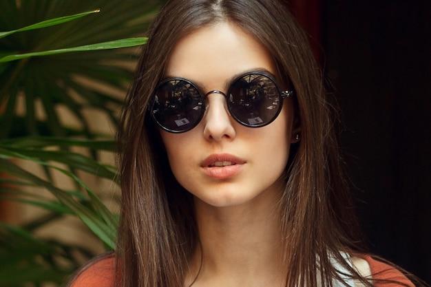 Persone, emozioni, naturale, bellezza e concetto di stile di vita - primo piano ritratto giovane ragazza in camicia bianca jeans e occhiali da sole, stile di moda vintage intorno alle palme. concetto di bellezza estiva
