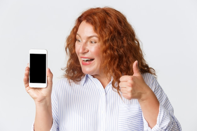 Persone, emozioni e concetto di tecnologia. primo piano di una donna di mezza età stupita ed eccitata, sorridente con i capelli rossi, che mostra i pollici in su di essere colpiti dall'app mobile, guardando lo schermo dello smartphone.