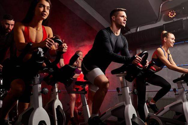 Persone che esercitano, allenamento cardio gambe in bicicletta in palestra, per una buona salute. culturista, stile di vita, esercizio fitness, allenamento e concetto di allenamento sportivo