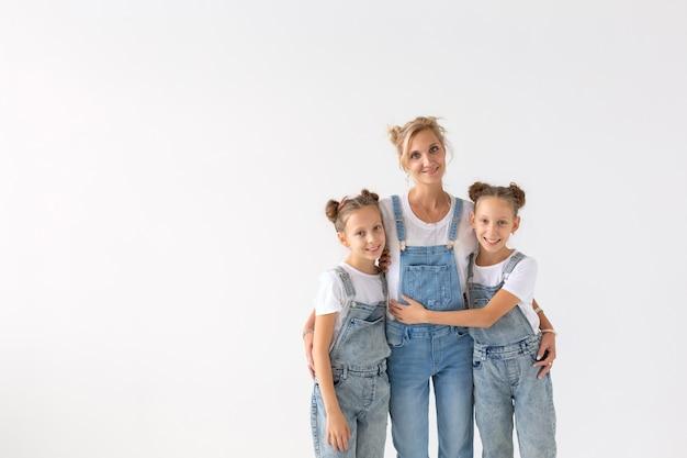 Concetto di persone, famiglia e bambini - sorelle gemelle con la loro mamma sul muro bianco con spazio di copia.