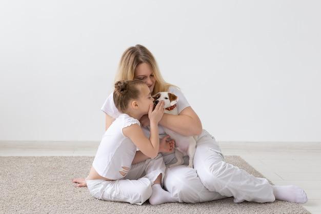 Concetto di persone, famiglia e animali domestici - madre e figlia seduta sul pavimento con il cucciolo jack russell