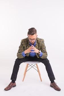 Concetto di persone, moda e bellezza - bel giovane uomo fiducioso seduto sulla sedia, isolato sul muro bianco