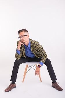 Concetto di persone, moda e bellezza - bel giovane uomo seduto sulla sedia, isolato su bianco