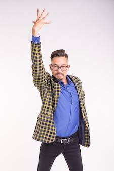 Persone, moda e concetto di espressione - ritratto di un giovane uomo barbuto divertente alla moda hipster su un muro bianco.