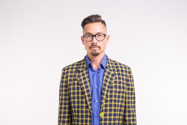 Concetto di persone, moda e stile - giovane uomo alla moda hipster su priorità bassa bianca.