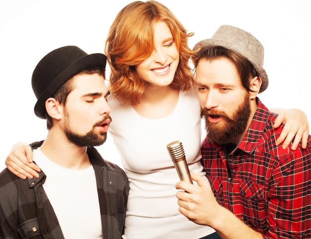 Concetto di persone, amicizia e tempo libero: gruppo di giovani amici felici che si divertono al karaoke, stile hipster.