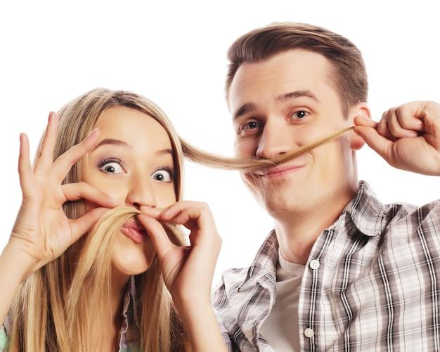 Concetto di persone, amicizia, amore e tempo libero - bella giovane coppia amorosa che fa baffi finti dai capelli mentre si trova isolato su bianco.