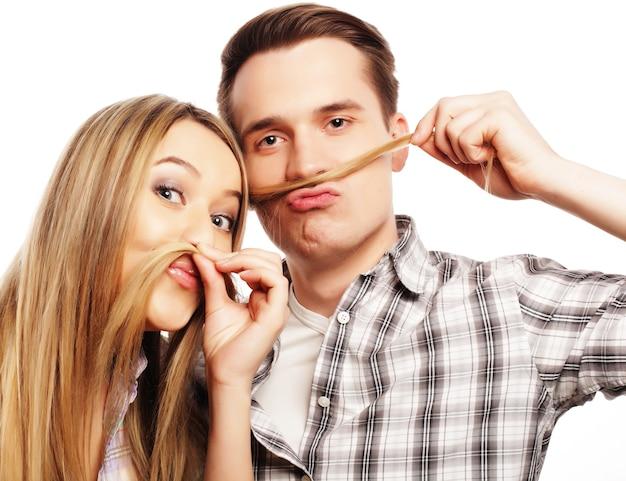 Persone, amicizia, amore e concetto di svago bella giovane coppia di innamorati che fa baffi finti dai capelli mentre si trova isolato su bianco.