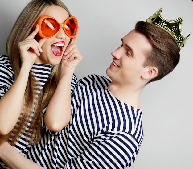 Persone, amicizia, amore e concetto di svago - bella giovane coppia di innamorati con microfono. grandi bicchieri e corona arancioni. pronto per la festa.