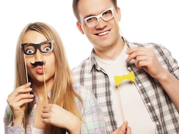 Concetto di persone, amicizia, amore e svago - coppia adorabile che tiene gli occhiali da festa sul bastone