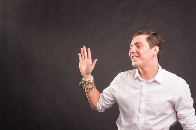 Persone, gesti e concetto di moda - giovane uomo bello che agita la mano su sfondo marrone con spazio copia