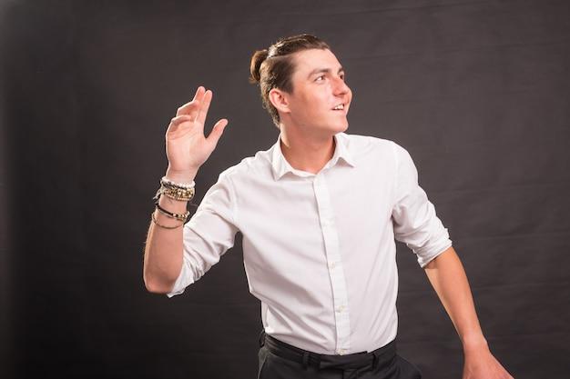 Persone, gesto e concetto di moda - giovane uomo bello agitando la mano su sfondo marrone.