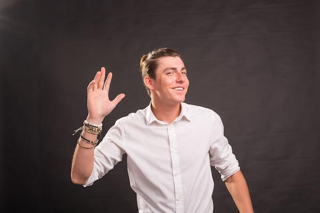 Persone, gesto e concetto di moda - giovane uomo bello agitando la mano contro il muro marrone.