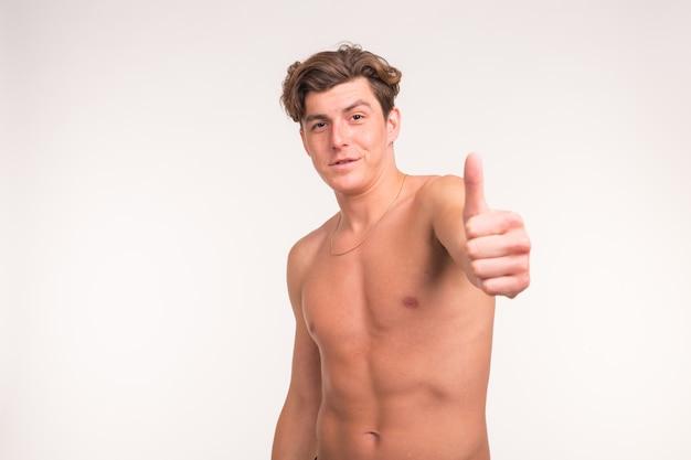Concetto di persone, gesto, fitness e sport - uomo senza camicia atletico che mostra pollice in su sopra il muro bianco.