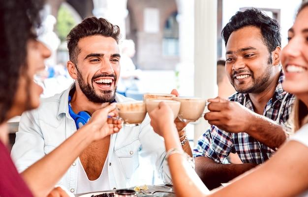 Gruppo di persone che beve latte al ristorante bar caffetteria - amici felici che parlano e si divertono insieme alla caffetteria dehors - concetto di stile di vita con uomini e donne felici al caffè