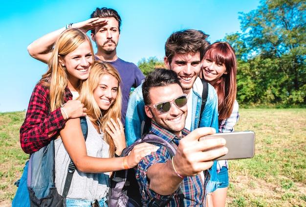 Gruppo di persone che prendono selfie durante un'escursione di trekking - felice amicizia e concetto di libertà con giovani amici millenari che si divertono insieme all'esperienza del campeggio - filtro vivido luminoso