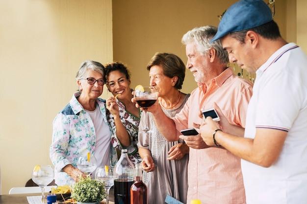 Gruppo di persone di età e sesso misti che si divertono insieme in amicizia per una cena o un pranzo