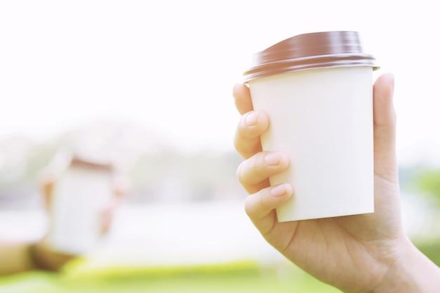 La gente mano che tiene il bicchiere di carta di asporto bere caffè