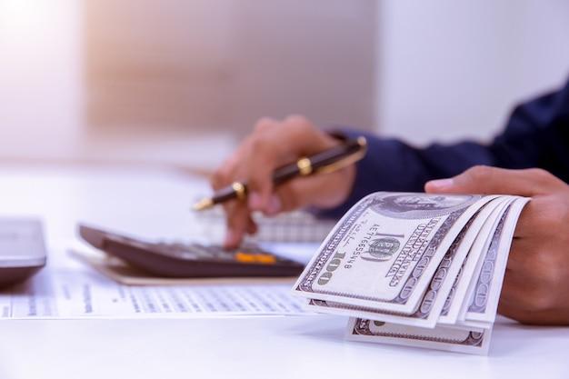 Calcolatrice di lavoro di mano di persone e dollari di denaro in finanza banking e concetto di risparmio.