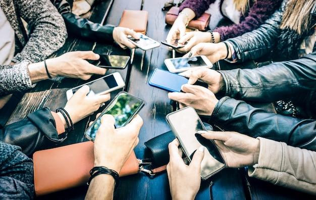 Mani di persone che hanno divertimento dipendente insieme utilizzando smartphone