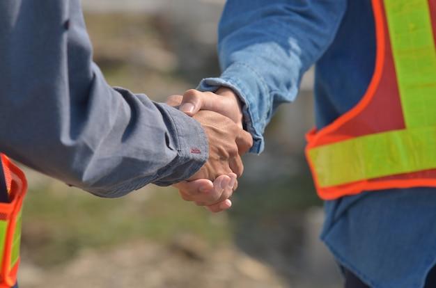 Le mani delle persone stringono il successo della partnership commerciale, il concetto di stretta di mano, la stretta di mano con ingegneri e architetti concordano con il successo del progetto di costruzione.