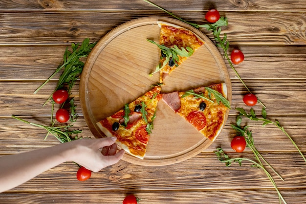 Mani della gente prendendo le ultime fette di pizza. la pizza e le mani si chiudono in su