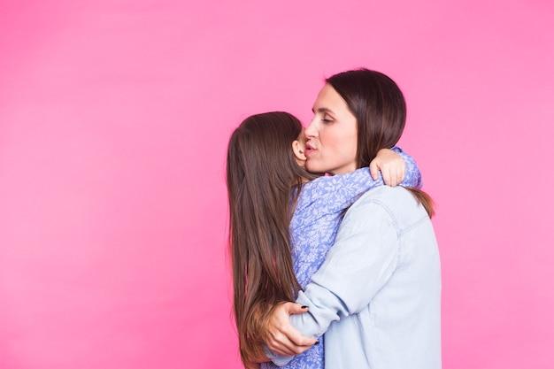 Concetto di persone, felicità, amore, famiglia e maternità. piccola figlia felice che abbraccia e bacia sua madre sopra il rosa con copyspace