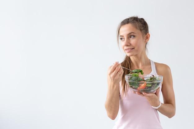 Persone, stile di vita sano e concetto di fitness - bella giovane donna dopo l'allenamento che mangia insalata sana sul muro bianco con lo spazio della copia
