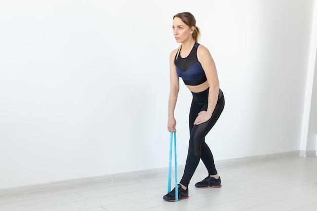 Persone, sano e concetto di sport - fit donna in abiti sportivi accovacciata con fascia