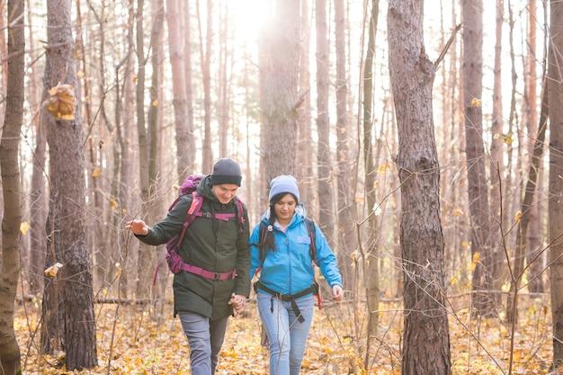 Concetto di persone, escursione, turismo e natura - escursionismo turistico di coppia nella foresta di autunno.